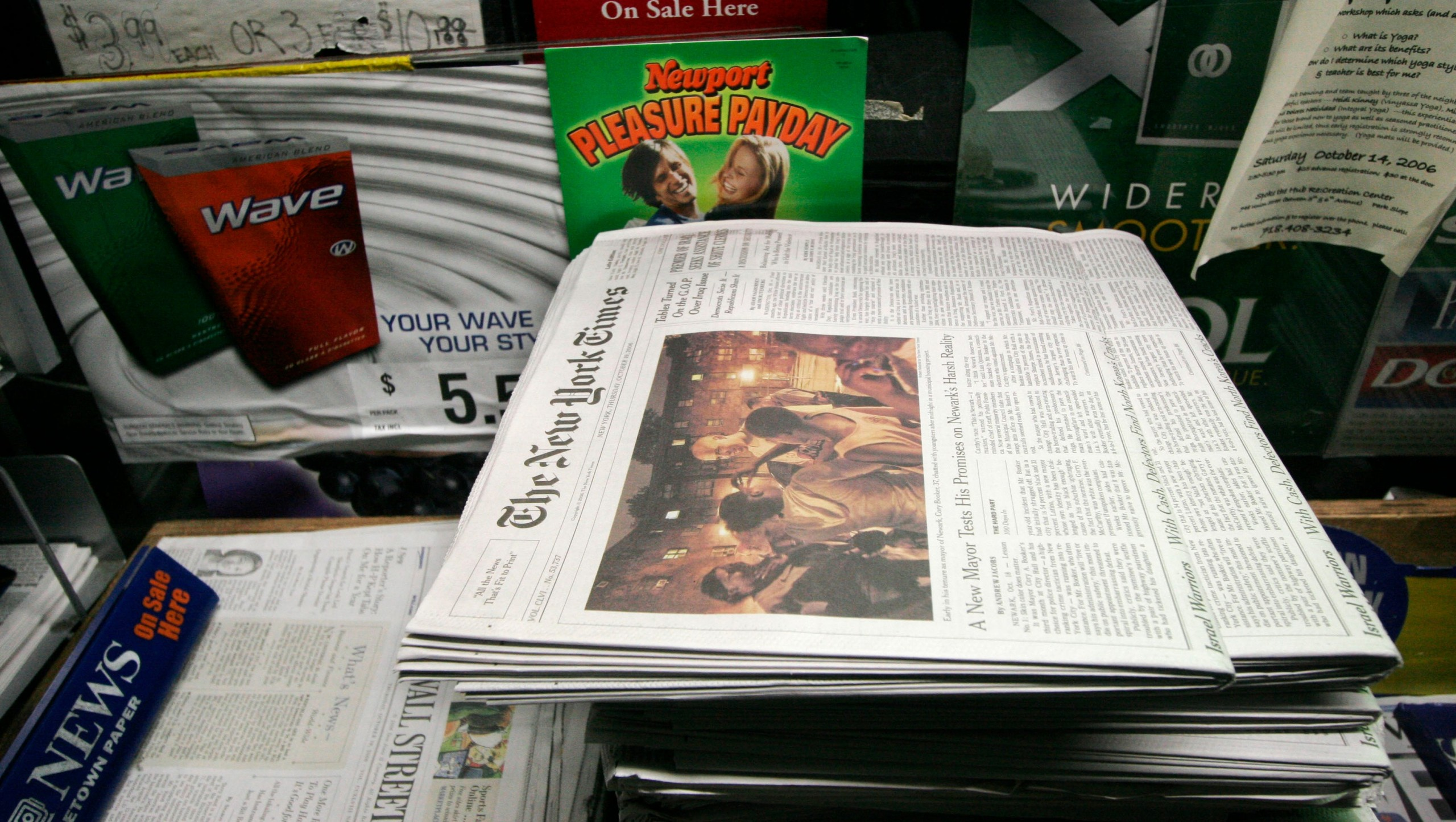 A newspaper with an open book on a table