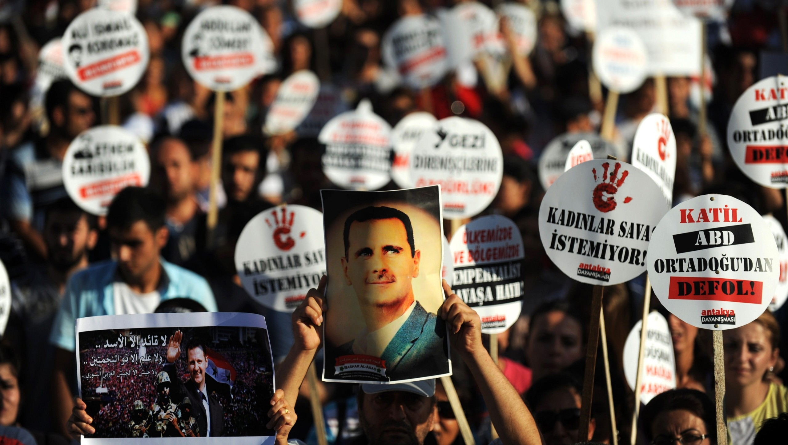 Bashar al-Assad et al. standing in front of a crowd