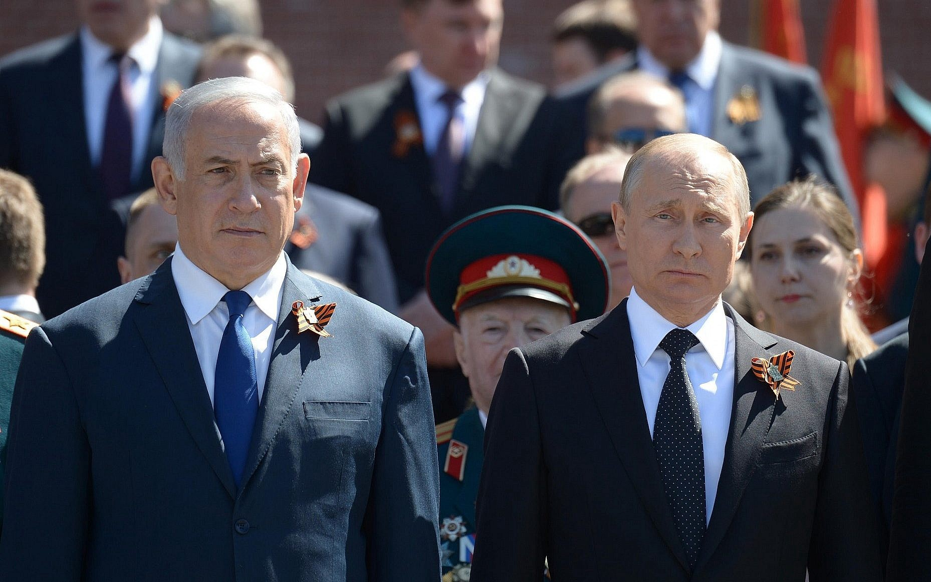 Benjamin Netanyahu wearing a suit and tie standing in front of a crowd