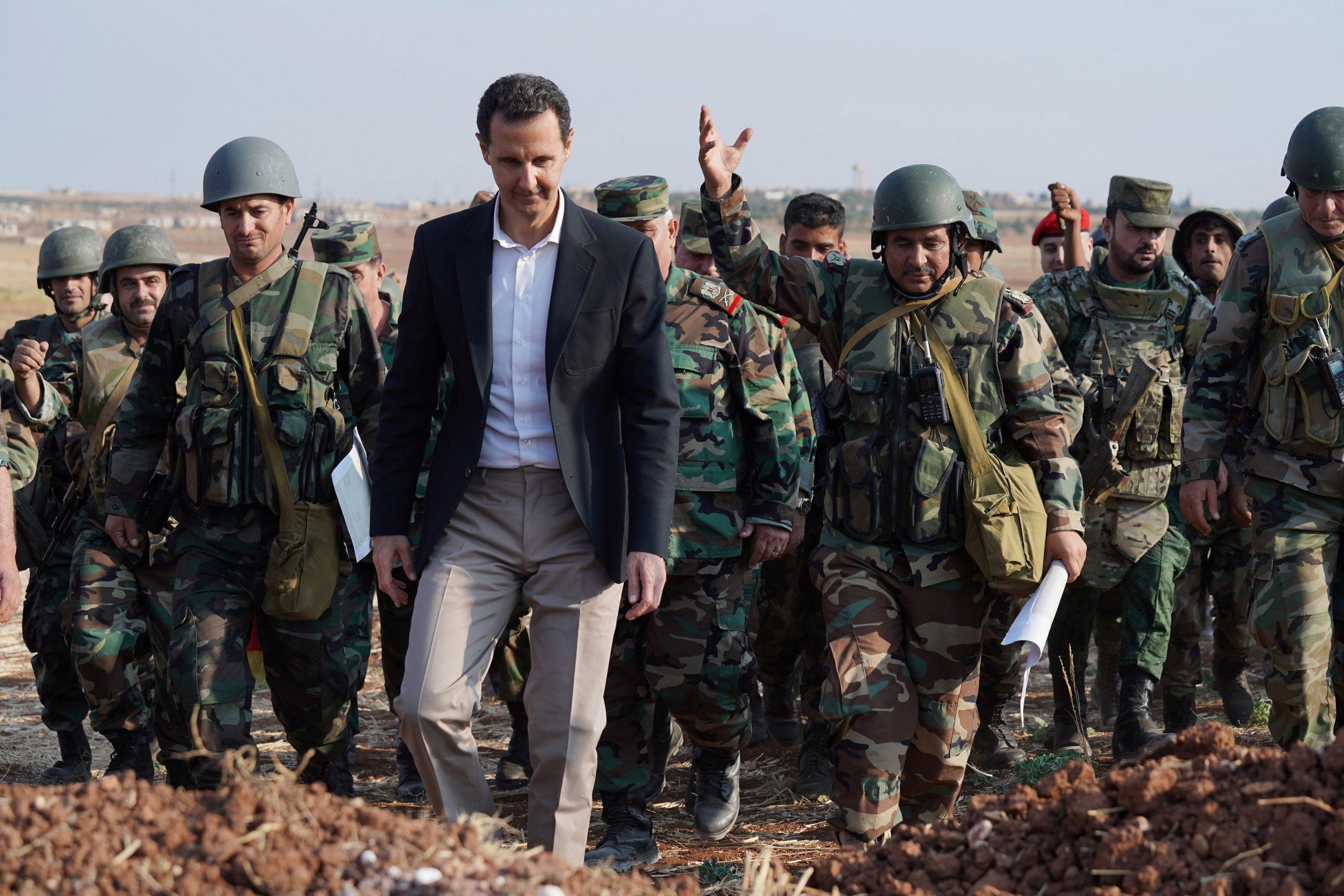 Bashar al-Assad et al. standing in front of a military uniform