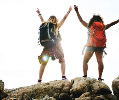 A two girls wearing a bags and standing on mountain