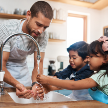A man and kids wash there hands under the tap