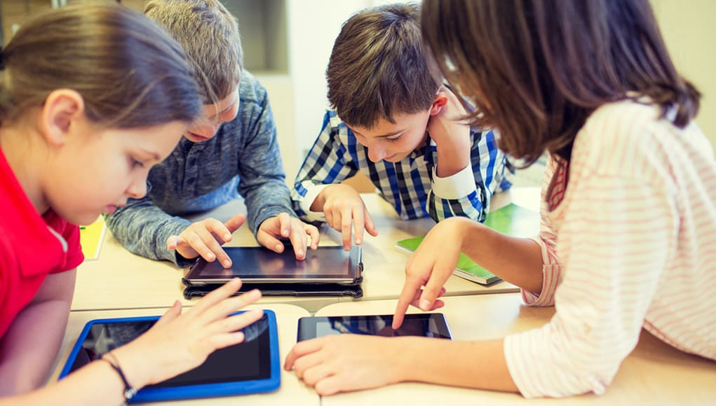 Elementary students having fun playing online games on tablets